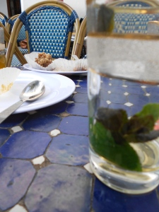 A drained glass of mint tea (sans sucre) and an empty plate, once occupied by pastries.